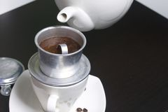O fabricante de café vietnamiano é equipado em um copo O café à terra é derramado nele Barista derrama a água a ferver do bule ne imagens de stock