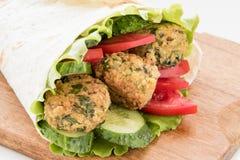 O Falafel e os legumes frescos rolaram no pão do pão árabe Fotos de Stock