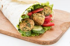 O Falafel e os legumes frescos rolaram no pão do pão árabe Fotografia de Stock