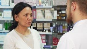 O farmacêutico atento dá a uma mulher um comprimido para tossir imagens de stock royalty free