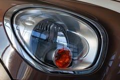 O farol de brilho à moda dianteiro da cor branca e vermelha é equipado no corpo com uma inscrição do desenhista dentro do mini tã imagens de stock