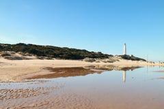 O farol do cabo de Trafalgar refletiu na água, nas costas do sul da Espanha Foto de Stock Royalty Free