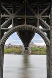 O farol vermelho pequeno sob a ponte cinzenta Fotos de Stock