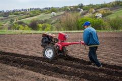 O fazendeiro ara a terra com um cultivador, preparando a para plantar vegetais Imagem de Stock