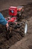O fazendeiro ara a terra com um cultivador, preparando a para plantar vegetais Foto de Stock