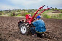 O fazendeiro ara a terra com um cultivador, preparando a para plantar vegetais Fotos de Stock Royalty Free