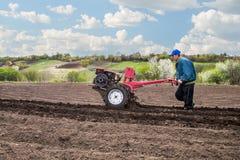 O fazendeiro ara a terra com um cultivador, preparando a para plantar vegetais Fotografia de Stock Royalty Free