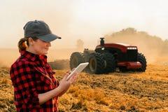 O fazendeiro da mulher controla um trator autônomo fotos de stock royalty free