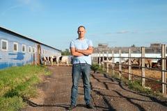 O fazendeiro está trabalhando na exploração agrícola com vacas de leiteria Foto de Stock