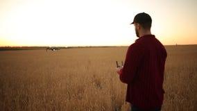 O fazendeiro guarda o controlador remoto com suas mãos quando o quadcopter voar no fundo O zangão paira atrás do video estoque