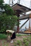 O fazendeiro idoso da mulher inspeciona as plantas plantadas no campo, sobre a ponte Fotos de Stock Royalty Free