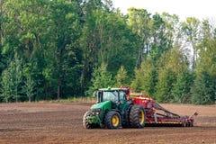 O fazendeiro no outono trata os campos com o trator e enriquece-os com adubos minerais imagens de stock