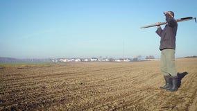 O fazendeiro segura a terra com uma enxada filme