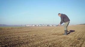 O fazendeiro segura a terra com uma enxada vídeos de arquivo
