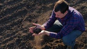 O fazendeiro toma uma amostra do solo fértil preto Punhado do fazendeiro do solo fértil que está no campo cultivado Solo filme