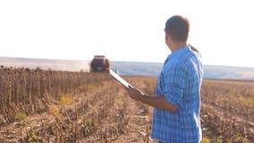 O fazendeiro trabalha o homem de cultivo esperto lido ou o girassol da colheita da análise um relatório no tablet pc em um campo  filme