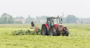 O fazendeiro usa o trator para espalhar o feno no campo fotografia de stock royalty free
