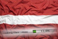 O fazendo download arquiva em um computador, bandeira de Letónia imagem de stock royalty free