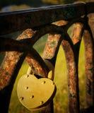 O fechamento amarelo no formulário do coração pendura na cerca oxidada velha fotografia de stock