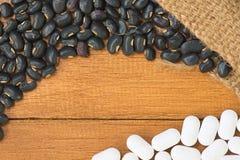O feijão preto derrama fora do saco com medicina branca sobre a parte superior da tabela de madeira alaranjada Foto de Stock