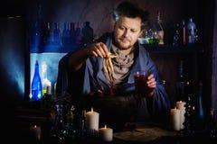 O feiticeiro fabrica cerveja uma poção imagem de stock