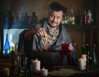 O feiticeiro fabrica cerveja uma poção fotos de stock