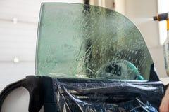 O feiticeiro para instalar o equipamento adicional cola um filme do matiz no vidro dianteiro lateral do carro e da água dos pulve fotografia de stock