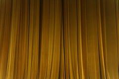 O feixe amarelo fechado do projetor do fundo da cortina iluminou O teatro drapeja fotografia de stock royalty free