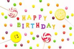 O feliz aniversario da frase, pirulitos, sorriso dos doces sobre Fotografia de Stock Royalty Free