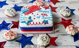4o feliz do bolo de julho cercado por queques Fotografia de Stock