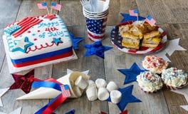 4o feliz do bolo de julho com queques, marshmallows e cachorros quentes Imagens de Stock Royalty Free