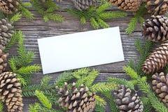 O Feliz Natal carda com agulhas e cones do pinheiro em de madeira Imagens de Stock Royalty Free