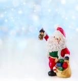 O Feliz Natal carda com estatueta de Santa Claus Ilumina o backgroun Imagem de Stock
