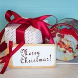 O Feliz Natal carda com um vintage Santa Candy Tin e o presente vermelho e branco do presente amarrado com uma curva vermelha do  Imagens de Stock Royalty Free