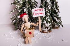 O Feliz Natal coloca estacas o sinal guardado pelo chapéu vestindo articulado de madeira de Santa que guarda um presente na cena  foto de stock