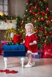 O Feliz Natal e boas festas menina bonito da criança pequena está decorando a árvore de Natal dentro fotografia de stock royalty free