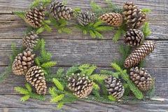 O Feliz Natal molda com agulhas e cones do pinheiro em de madeira Fotografia de Stock Royalty Free