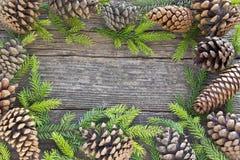 O Feliz Natal molda com agulhas e cones do pinheiro em de madeira Fotografia de Stock