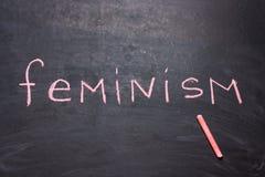 O feminismo da palavra é escrito o giz O conceito da igualdade fotos de stock