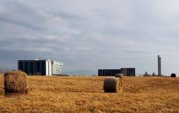O feno rola em um campo do inverno na frente do distrito futurista de Feletto Umberto, perto de Udine, em Itália Foto de Stock Royalty Free