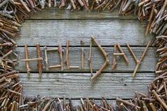 O feriado da inscrição com as varas de madeira no fundo de madeira Imagem de Stock