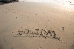 O feriado escrito na areia na praia acena no fundo Fotos de Stock Royalty Free