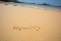 O feriado escrito na areia na praia acena no fundo Imagem de Stock