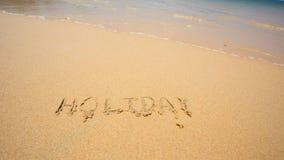 O feriado escrito na areia na praia acena no fundo Fotografia de Stock Royalty Free