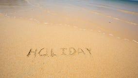 O feriado escrito na areia na praia acena no fundo Foto de Stock Royalty Free