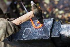 O ferreiro forja a curvatura do ferro com o martelo no batente Imagem de Stock