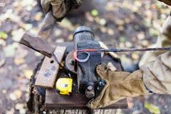 O ferreiro forja a haste de ferro vermelha quente no torno Foto de Stock Royalty Free