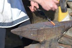 O ferreiro martela o ferro encarnado em um batente Imagens de Stock Royalty Free