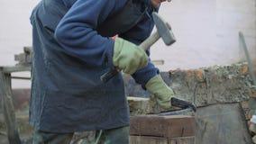 O ferreiro novo trabalha o metal Artesão, escocês na forja privada na vila Dando forma ao boleto do metal vídeos de arquivo