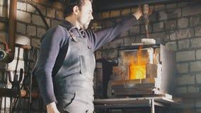 O ferreiro regula o fogo na fornalha com metal quente imagens de stock